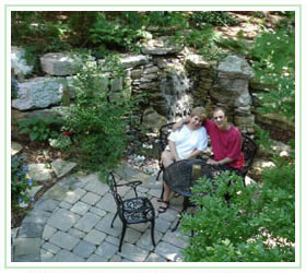 Satisfied customers sitting at wrought iron table on flagstone patio beside waterfall